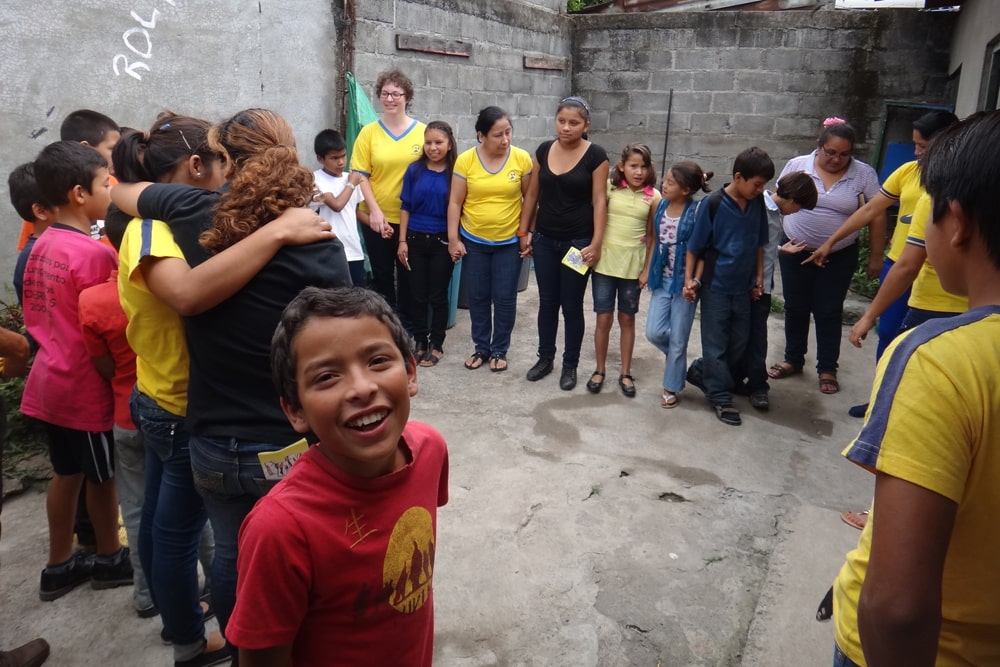 Children and adolecents stand in a backyard of a house in a circle holding hands. Some of them wear blue and yellow shirts.