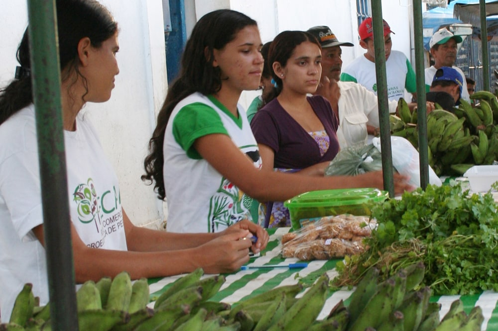 Young women sell their bananas in a marketbooth.