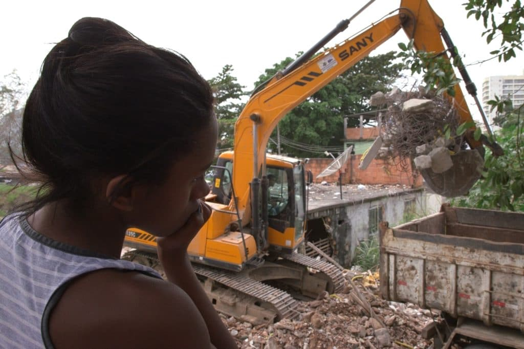 Naomy a darkskinned girl watches the excavator tearing down walls of a broken small house.