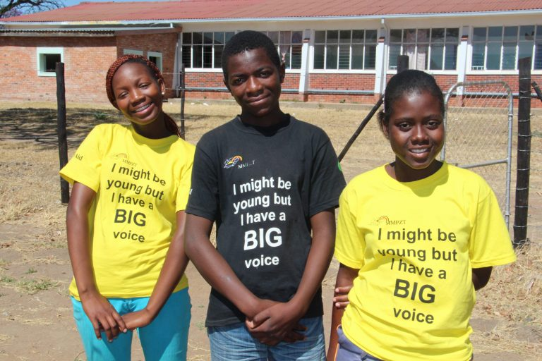 Three teenagers with black and yellow T-shirts. Print: I might be young but I have a BIG voice.